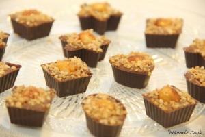 coques en chocolat pralinées surmontées d'une noisette grillée caramélisée et saupoudrées de pralin